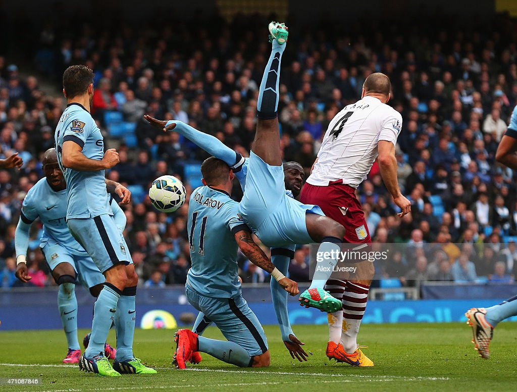 Yaya Toure of Manchester City tangles with Ron Vlaar of Aston Villa and team mate Aleksandar Kolarov of Manchester City during the Barclays Premier League match between Manchester City and Aston Villa at Etihad Stadium on April 25, 2015 in Manchester, England.