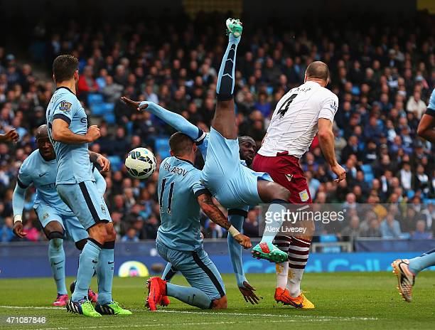 Yaya Toure of Manchester City tangles with Ron Vlaar of Aston Villa and team mate Aleksandar Kolarov of Manchester City during the Barclays Premier...