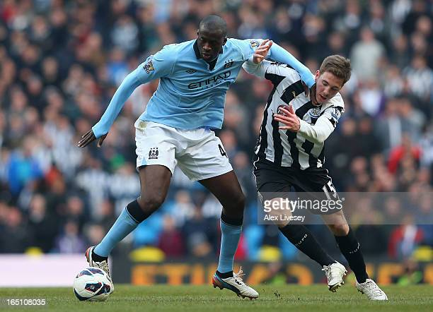 Yaya Toure of Manchester City tussles for posession with Dan Gosling of Newcastle United during the Barclays Premier League match between Manchester...