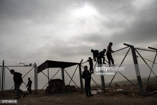 Yazidi children play along the barbed wire fence surrounding a camp for internally displaced outside of Dohuk Northern Iraq January 23 2016 ISIS...