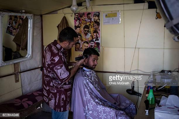 Yazidi man has his haircut at a makeshift hair salon at an IDP camp for Yazidi people on November 12 2016 in Sharya Iraq In 2014 thousands of Yazidi...