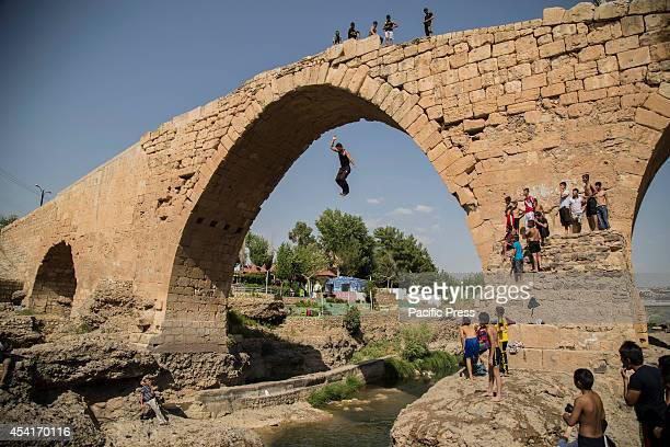 Yazidi refugees and local Kurdish youths take a bath from the scorching temperatures and enjoy swimming and diving in the Euphrates River at Delal...