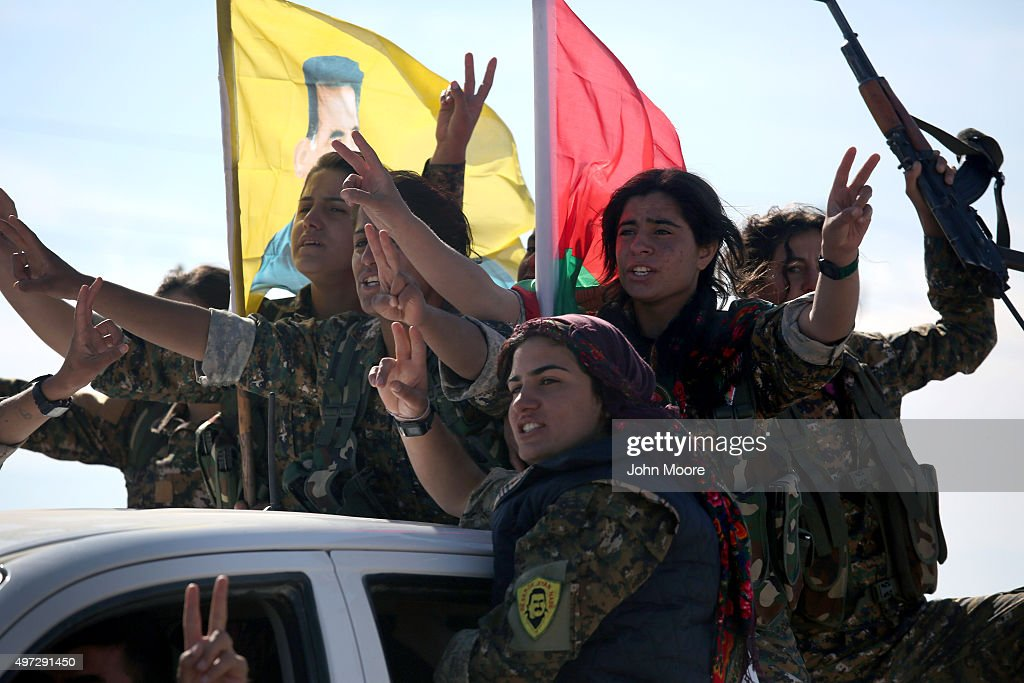 Yazidi soldiers cheer a fallen comrade on November 15, 2015 near Sinjar, Iraq. Kurdish forces, with the aid of massive U.S.-led coalition airstrikes, liberated Sinjar from ISIL extremists, known in Arabic as Daesh, in recent days. Local Yazidi fighters who fought with Kurdish forces have been taking any salvagable items out of the rubble, the town being uninhabitable and perilously close to the frontline.