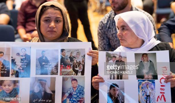 Yazidi women hold up pictures of missed relatives during a commemoration ceremony in Stuttgart, southern Germany, on August 3, 2019. - The Central...