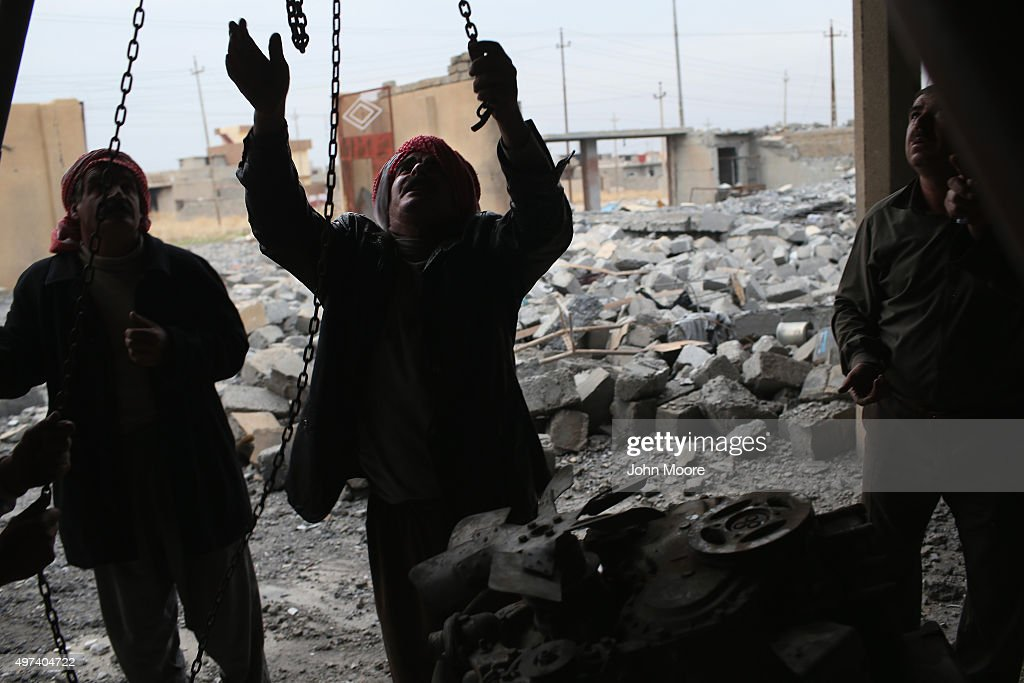 Yazidis work to lift an engine to salvage it from the rubble of an auto repair shop destroyed by an airstrike on November 16, 2015 in Sinjar, Iraq. Kurdish forces, with the aid of months of U.S.-led coalition airstrikes, liberated the town from ISIL extremists, known in Arabic as Daesh, in recent days. Although the battle was deemed a major victory, much of the city lay in complete ruins.