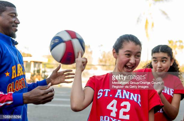 Yazmin Lopez center of the St Anne Lady Royals reacts after Buckets Blakes of the Harlem Globetrotters left attempts to teach her how to spin the...