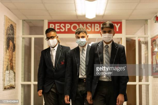 Year 10 pupils wear face masks as a precaution against the transmission of the novel coronavirus as they walk in a corridor at Moor End Academy in...
