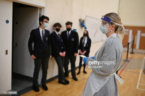 Year 10 students wait in line to take lateral flow Covid-19 tests in the Sports Hall at Park Lane Academy in Halifax, northwest England on March 17,...