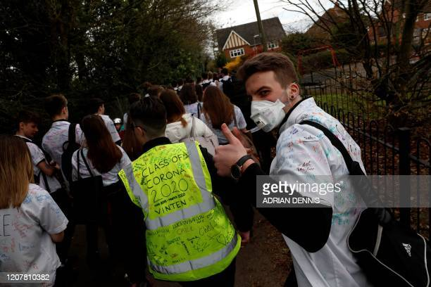 TOPSHOT Year 11 pupils some with graffiticovered shirts reading 'Survivor 2020' and 'Class of Corona 2020' react as they leave a secondary school in...