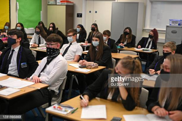 Year 11 students, wearing face coverings, take part in a GCSE maths class at Park Lane Academy in Halifax, northwest England on March 8, 2021 as...