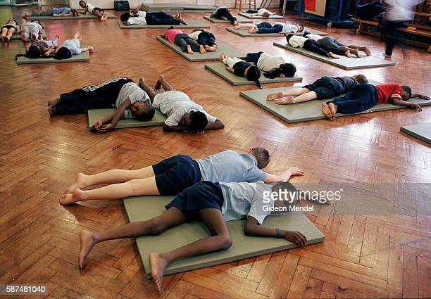 Year 4 pupils at Millfields Community School lie in deep relaxation at the end of an energetic PE movement class where they had been practicing...