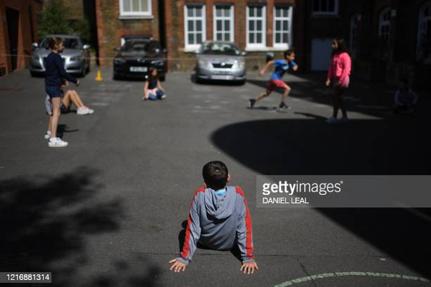 Year 6 child rests while playing outside at the College Francais Bilingue De Londres French-English bilingual school in north London on June 2, 2020...
