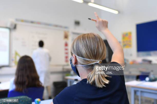 A Year 6 pupil wearing a face mask raises a hand to ask a question in a classroom at the College Francais Bilingue De Londres FrenchEnglish bilingual...