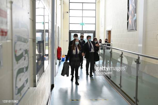 Year 9 class walk along a corridoor at Park Lane Academy in Halifax, northwest England on March 4, 2021. - England prepares to reopen schools to...