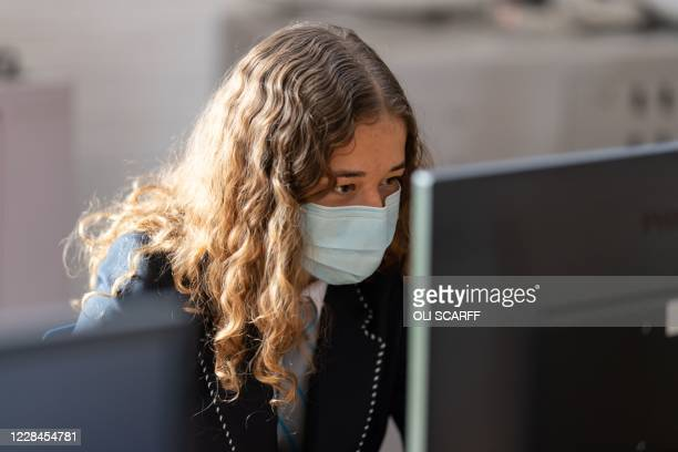 Year eight pupil wearing a face mask as a precaution against the transmission of the novel coronavirus works on a computer in the library of Moor End...