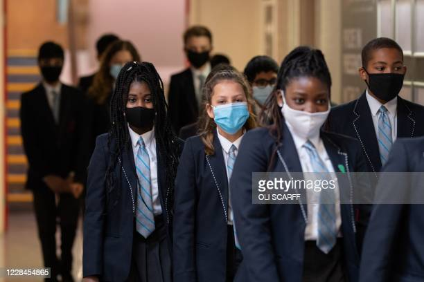 Year eight pupils wear face masks as a precaution against the transmission of the novel coronavirus as they walk along a corridor of Moor End Academy...