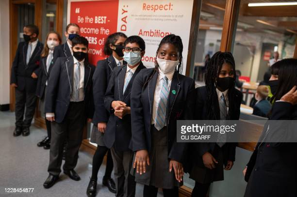 Year eight pupils wear face masks as a precaution against the transmission of the novel coronavirus as they chat in a corridor of Moor End Academy in...