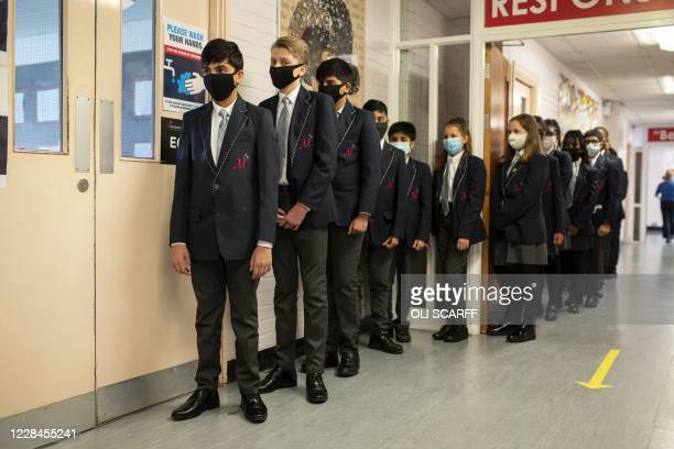 Year eight pupils wear face masks as a precaution against the transmission of the novel coronavirus as they queue in a corridor before attending an...