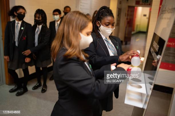 Year eight pupils wearing face masks as a precaution against the transmission of the novel coronavirus sanitise their hands in a corridor at Moor End...