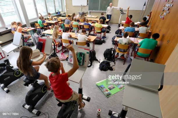 Year five pupils attend a German class while sitting on a bicycle at the FriedrichDessauerGymnasium in Aschaffenburg Germany 19 July 2017 The...