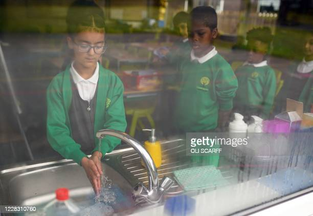 Year Four children wash their hands in their classroom after a break at Greenacres Primary Academy in Oldham, northern England on September 02, 2020....