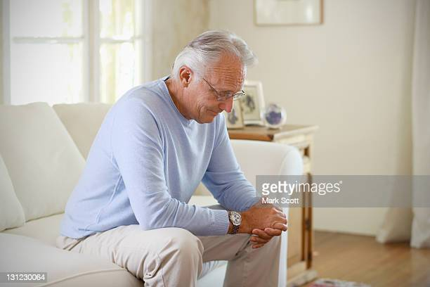 60 year man sitting on couch deep in thought