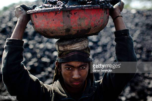 12 year old Abdul Kayum from Assam pauses for a portrait whilst working at a coal depot carrying coal to be crushed on April 15 2011 near Lad Rymbai...