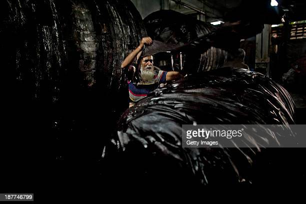63 year old Abu Talib unloads leather hides from a vat of chemical mixture in a tannery the Phoenix Leather Complex November 10 2013 in the...