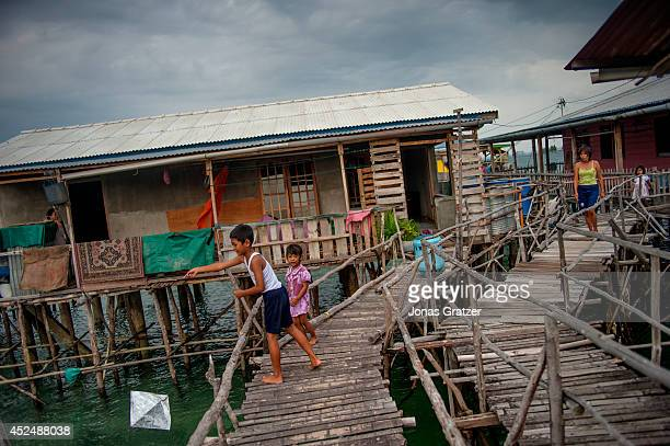 10 year old Addi and his little sister play with a dragon kite on the island of Belakang Padang where many pirates used to hide their weapons and...