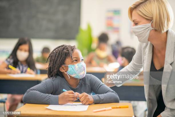 6 year old, african american student wearing a protective face mask in class - instructor stock pictures, royalty-free photos & images