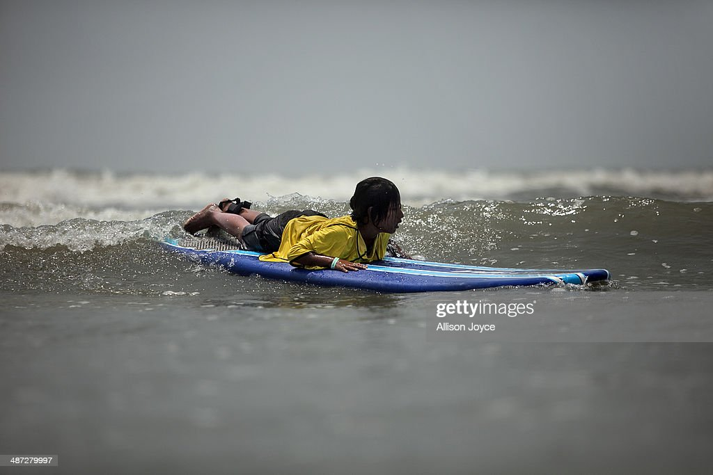 COX'S BAZAR, BANGLADESH - APRIL 24: 10 year old Aisha competes during the annual Cox's Bazar surf competition April 24, 2014 in Cox's Bazar, Bangladesh. A group of 10-12 year old female beach vendors, most of whom have dropped out of school to help support their families, have been learning to surf for the past three months in preparation for the annual Cox's Bazar surf competition. 24 year old surfer, lifeguard and beach worker Rashed Alam, has been teaching and mentoring the girls for 3 months. Like the girls, Alam dropped out of school and started working on the beach to help support his family at a young age. He started surfing when he was 16. He says that his way of giving back is by ensuring that girls get a good future through surfing.