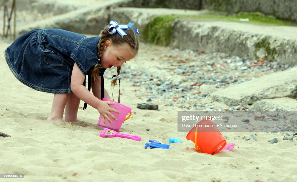 3 year old Amber Broadfoot from Crosby, Merseyside, plays in the sand on Crosby beach during the warm weather.