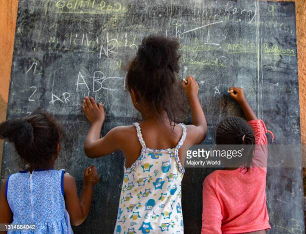 Year old Amilia, revising with her sisters Kalena and Barbie at home. Due to the coronavirus outbreak nursery schools are still closed in Rwanda and...