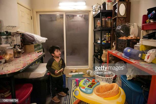 2 year old Amirul watches TV on a phone while his mother cooks dinner on January 12 2019 in Chicago Illinois The Shukor family arrived in Chicago in...