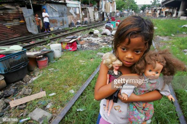 6 year old Anna Ramiento holds her dolls near her shack along the railroad tracks where hundreds of poverty stricken live in the slums on July 14...
