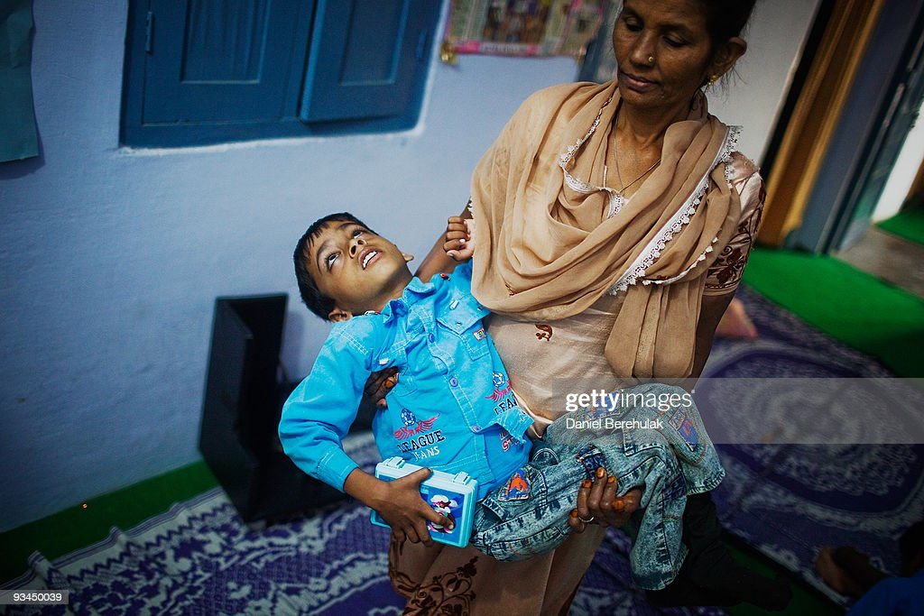 8 year old Annan is carried by Nafiza Bee co-ordinator of the Chingari Trust clinic on November 27, 2009 in Bhopal, India. Twenty-five years after an explosion causing a mass gas leak, in the Union Carbide factory in Bhopal, killed at least eight thousand people, toxic material from the biggest industrial disaster in history continues to affect Bhopalis. A new generation is growing up sick, disabled and struggling for justice. The effects of the disaster on the health of generations to come, both through genetics, transferred from gas victims to their children and through the ongoing severe contamination, caused by the Union Carbide factory, has only started to develop visible forms recently. Annan suffers from cerebral palsy and receives vital rehabilitative support and care at the Chingari Trust Clinic.