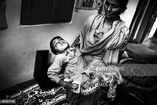 8 year old Annan is carried by Nafiza Bee coordinator of the Chingari Trust clinic on November 27 2009 in Bhopal India Twentyfive years after an...
