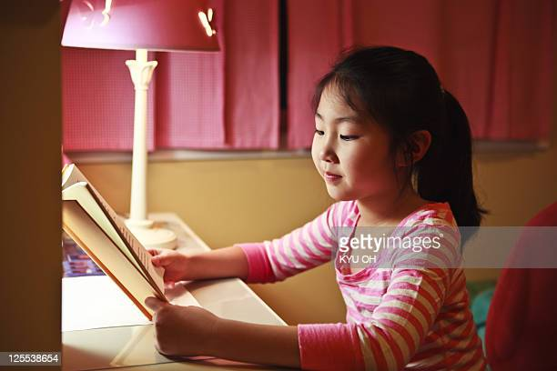 7 year old Asian girl reading a book at night.