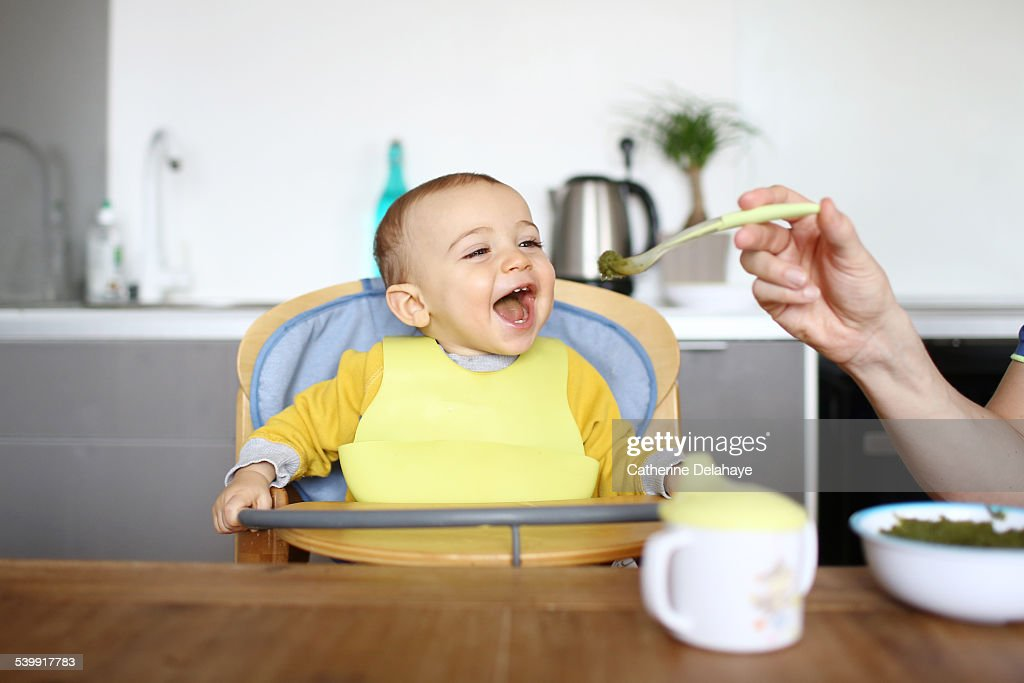 A 1 year old baby boy eating in his high chair : Stock Photo
