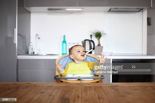 A 1 year old baby boy in his high chair