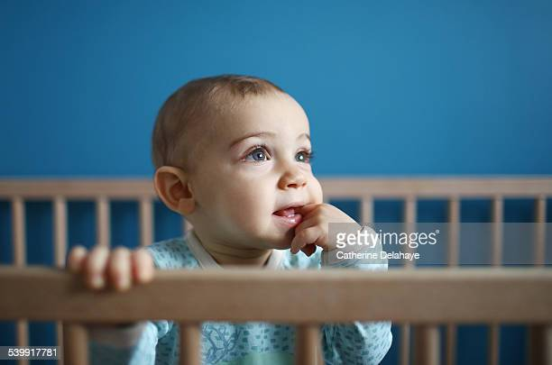 A 1 year old baby boy in his playpen