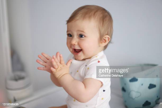 a 1 year old baby girl clapping her hands on her baby-changing table - clapping hands stock pictures, royalty-free photos & images