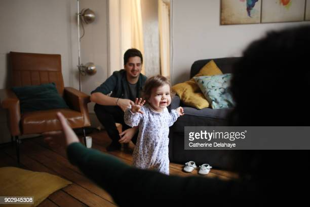 a 1 year old baby girl is taking her first steps at home - primeiros passos - fotografias e filmes do acervo