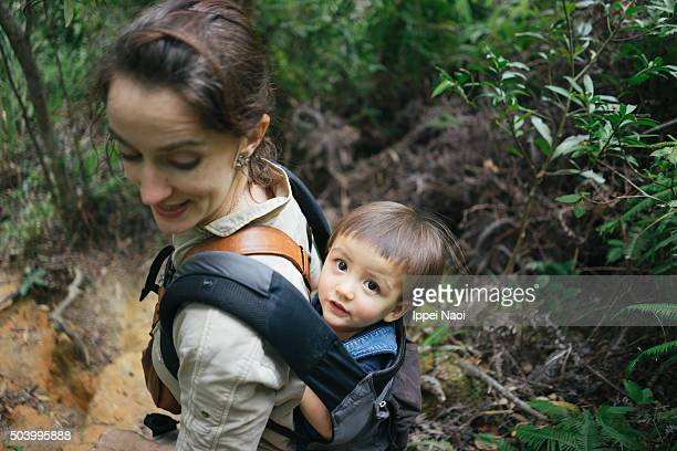 1 year old baby girl on mother's back and looking at camera during hiking
