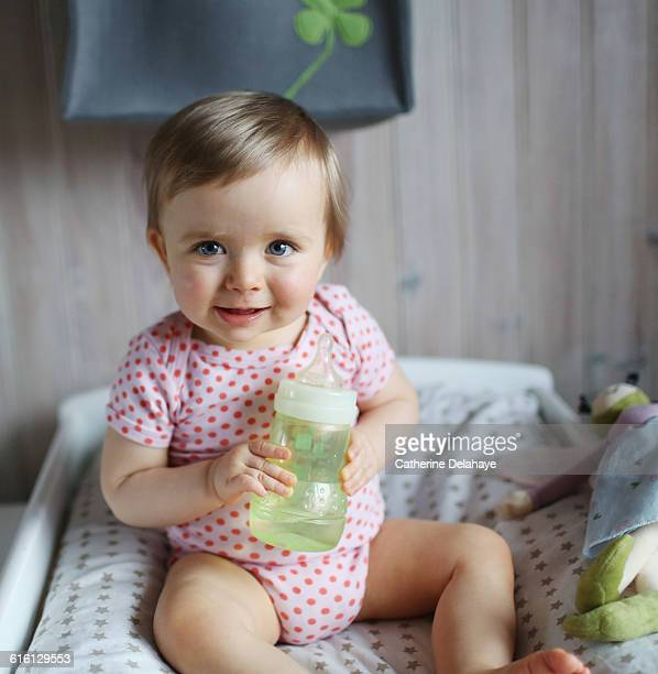 A 1 year old baby girl with a bottle