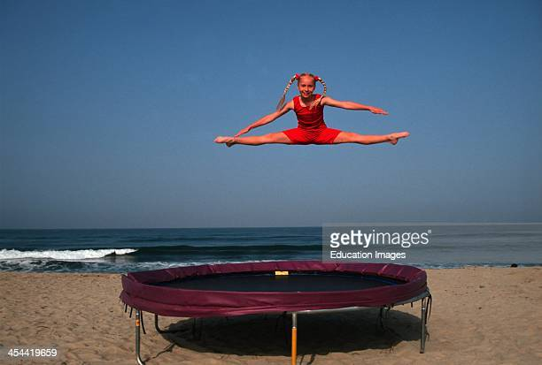 10 Year Old Blonde Girl Doing Splits In The Air Above Trampoline On Beach