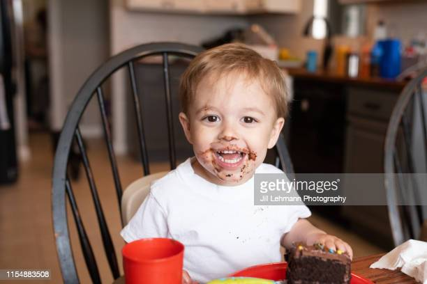 3 year old blonde male toddler smiles with chocolate cake all over his face during his birthday party - sugar baby imagens e fotografias de stock