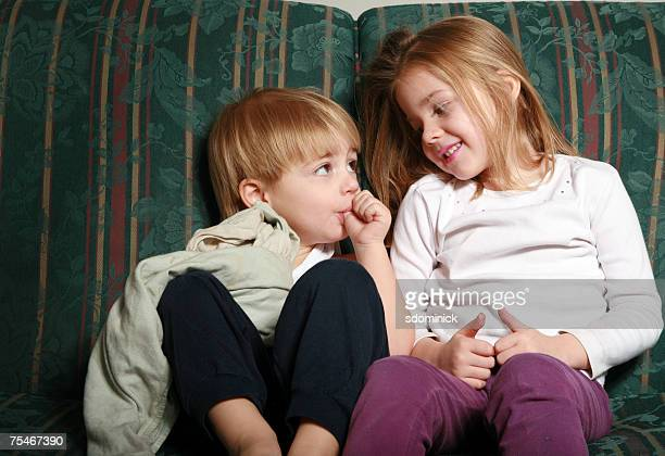 3 year old boy and 5 year old girl sitting on a couch