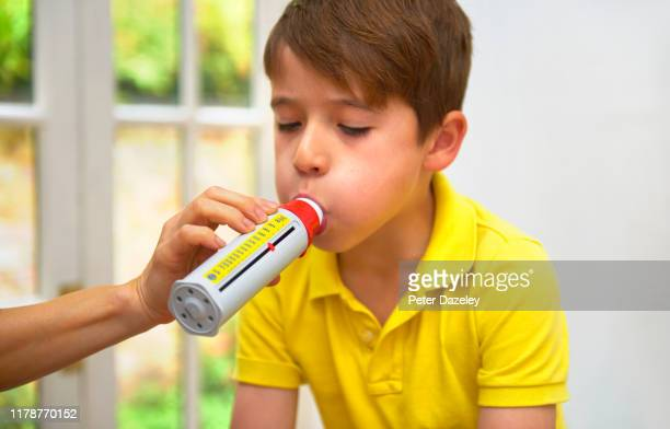 8 year old boy blowing into peak flow meter held by doctor/mother - urgency stock pictures, royalty-free photos & images