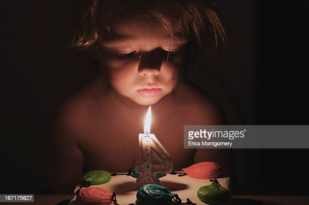 4 year old boy blows out candles in the dark - candle in the dark imagens e fotografias de stock